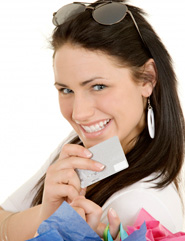 Excited young woman holding a gift card and bags