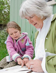 Mature woman looking through catalog with grandchild outdoors
