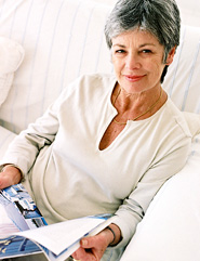 Mature woman looking up at camera holding a brochure