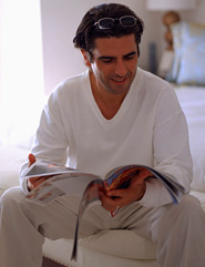 Man sitting on edge of the bed looking at catalog